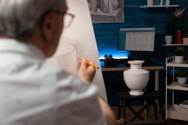 Кавказский художник смотрит на вазу на столе и рисует на холсте