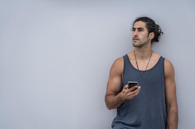 Кавказский спортсмен мужчина со смартфоном на тренировке
