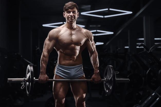 上腕二頭筋をポンピングする運動をしている白人アスリートの男性。 6パック、完璧な腹筋を備えた強力なボディービルダー。フィットネスとスポーツのコンセプト