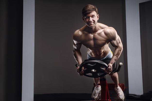 筋肉をポンピングする運動をしている白人アスリートの男性。 6パック、完璧な腹筋を備えた強力なボディービルダー。フィットネスとスポーツのコンセプト