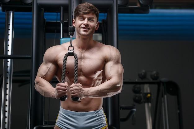 上腕三頭筋をポンピングする運動をしている白人アスリートの男性。 6パック、完璧な腹筋を備えた強力なボディービルダー。フィットネスとスポーツのコンセプト