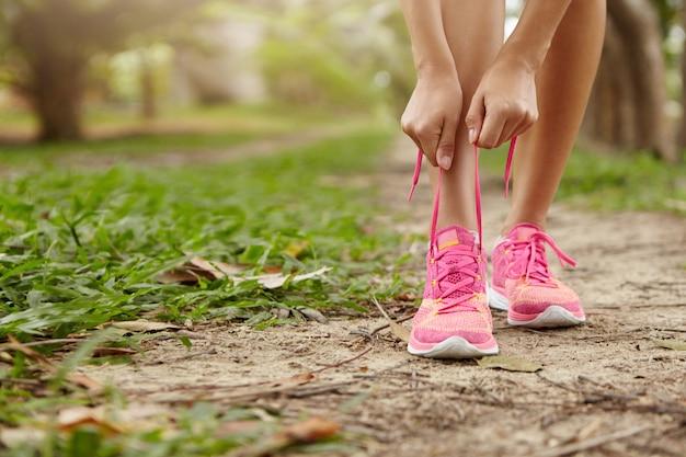 森の小道に立ってジョギングする前に彼女のピンクのランニングシューズのひもを結ぶ白人の運動女性。田舎でトレーニングをしながらスニーカーをひもで締める女性ランナー。