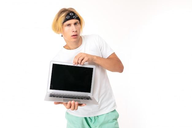 白い背景の上のレイアウトでバナーとノートパソコンの画面を示す白人の魅力的な金髪の男