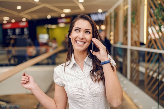 Caucasian attractive brunette with toothy smile using smart phone for gossiping while standing at shopping mall.
