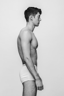Caucasian attractive man with a perfect body standing in underwear