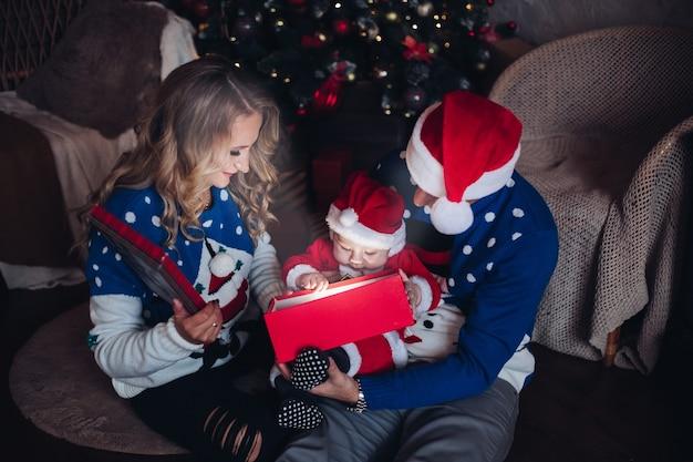 白人の魅力的なお母さん、ハンサムなお父さんと彼らのかわいい赤ちゃんは贈り物を開梱します