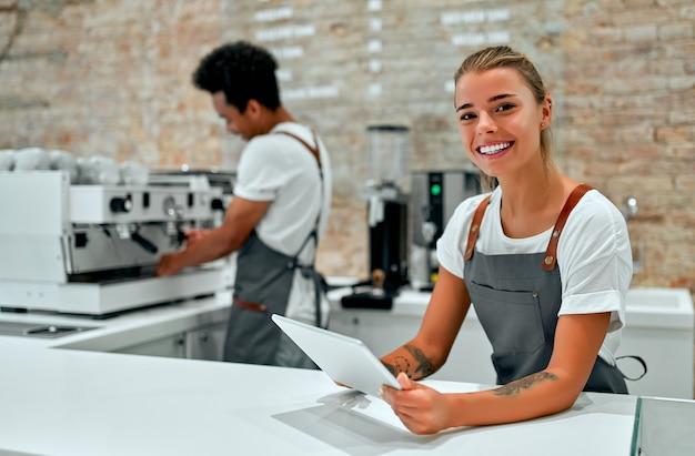 백인 매력적인 여성 바리스타는 커피숍의 카운터에서 손에 태블릿을 들고 서 있습니다.