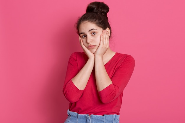 Caucasian attractive young woman wearing red stylish shirt, lady with hair bun