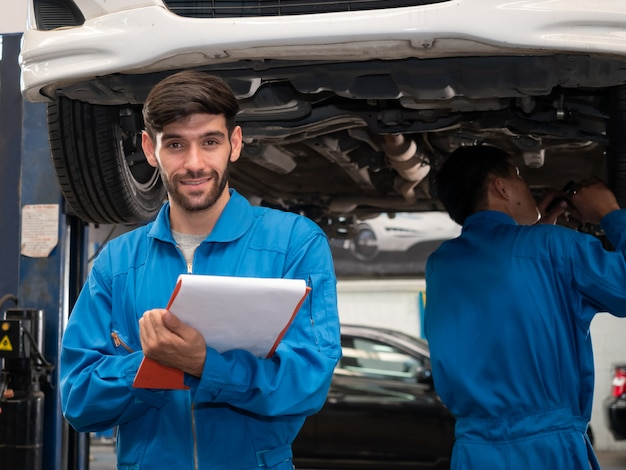 Кавказский автомеханик в форме проведения буфера обмена служебного порядка, работающих в гараже. техник, чеклист по ремонту машины, авто в гараже.