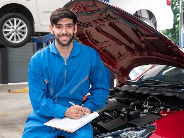 ガレージで働くサービス注文のクリップボードを保持している制服を着た白人の自動車整備士。ガレージで車を修理するための技術者チェックリスト。