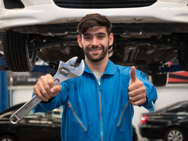 Caucasian auto mechanic in uniform holding wrenches and showing thumbs up in the garage. repair, car service and maintenance concept