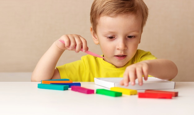 Caucasian baby blond sculpts from children's dough for sculpting at home at the table, children and creativity, the development of fine motor skills