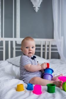 스트라이프 죄수 복에 파란 눈을 가진 백인 아기는 침대에 앉아 플라스틱 장난감을 가지고 노는