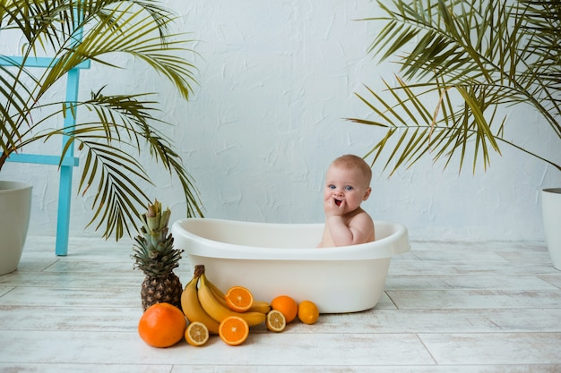 Caucasian baby boy with blue eyes sits in a white tub with tropical fruits on a white surface with a place for text