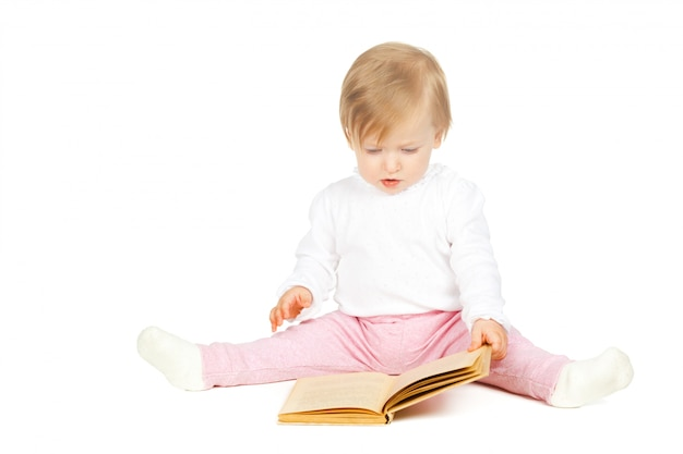 Caucasian baby girl holding a book isolated on white