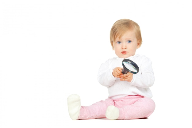 Caucasian baby girl holding magnifying glass isolated on white background