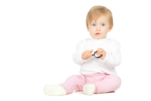 Caucasian baby girl holding magnifying glass isolated on white