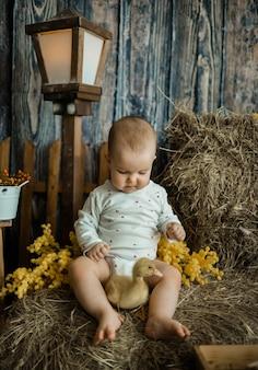 Кавказская девочка в белом боди сидит на стоге сена с желтым утенком в деревенском стиле