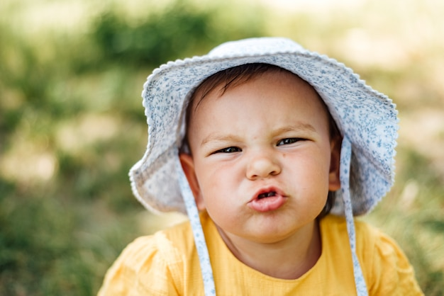 Caucasian baby girl is grimacing to the camera in hat and yellow dress