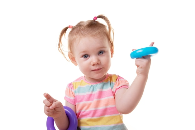 Caucasian baby girl playing with circles from children's educational toys and looking on the camera