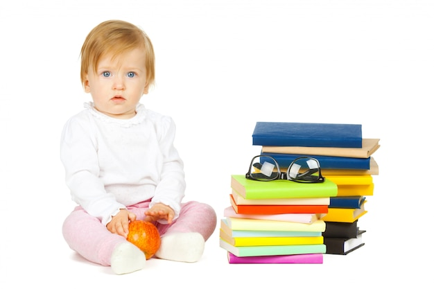 Caucasian baby girl with stack of books isolated on white
