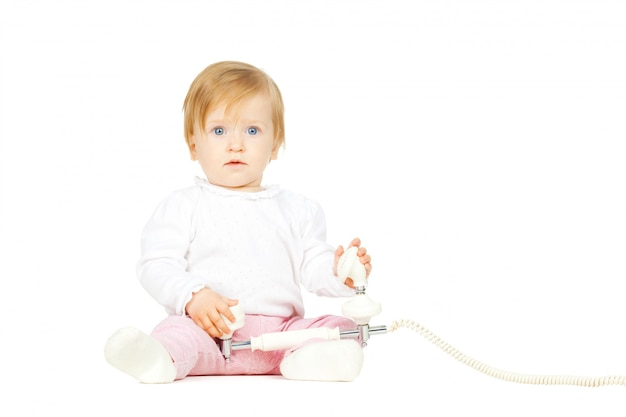 Caucasian baby girl with white retro telephone isolated on white background