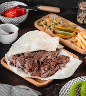 Caucasian barbecue kebab in lavash with french fries and pickles.
