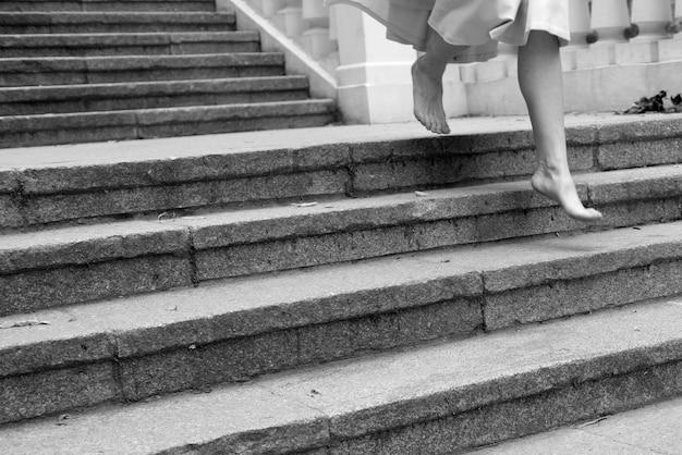 Caucasian barefoot woman walking down on steps alone.