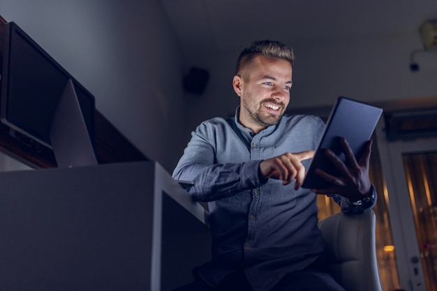 Caucasian bearded freelancer with toothy smile sitting in office late at night and using tablet.