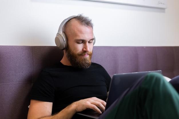 Uomo barbuto caucasico in cuffie in camera da letto sul letto che lavora al computer portatile da casa, digitando, pensando.