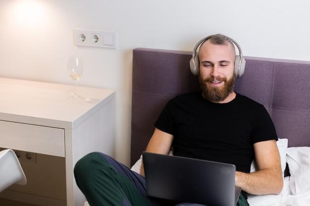 가정에서 노트북에서 일하고, 입력, 생각하는 침대에 침실에 헤드폰에 백인 수염 남자.