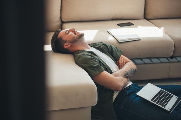 白人のひげを生やした男は、交差した手で床に疲れを感じてラップトップで仕事を終えて幸せです