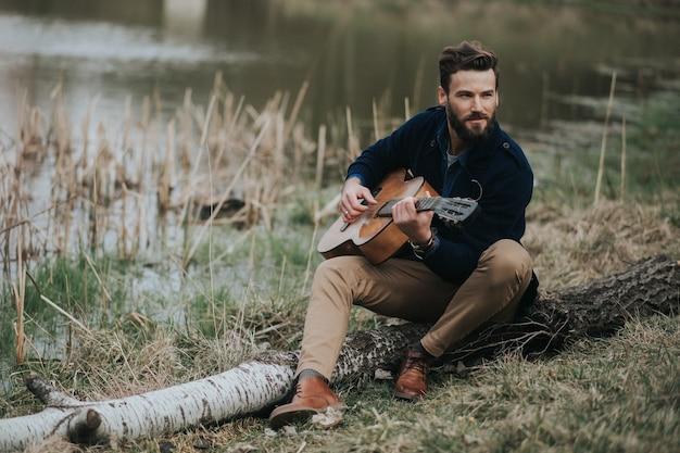 白人のひげを生やした男が湖の近くでギターを弾いています。ハンサムでスタイリッシュなヒップスター。