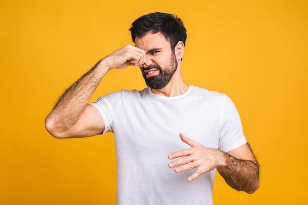 黄色の背景の上に孤立した白人のひげを生やした男は、臭くて嫌な、耐えられない匂いを嗅ぐ