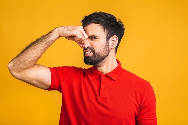 Caucasian bearded man isolated over yellow background smelling something stinky and disgusting