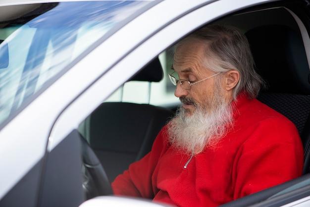 Caucasian bearded senior man with eyeglasses driving his car