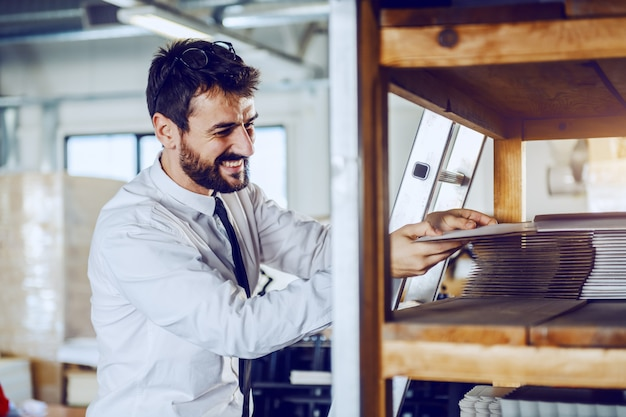 Caucasian bearded supervisor taking printing plate while standing in printing shop.