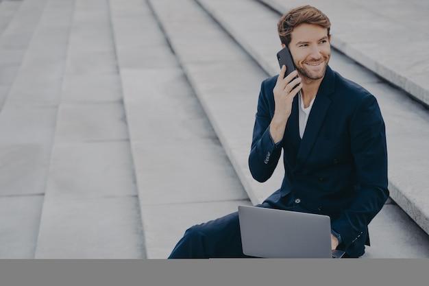 Кавказский бородатый молодой человек сидит на ступеньках на открытом воздухе с ноутбуком и разговаривает по мобильному телефону