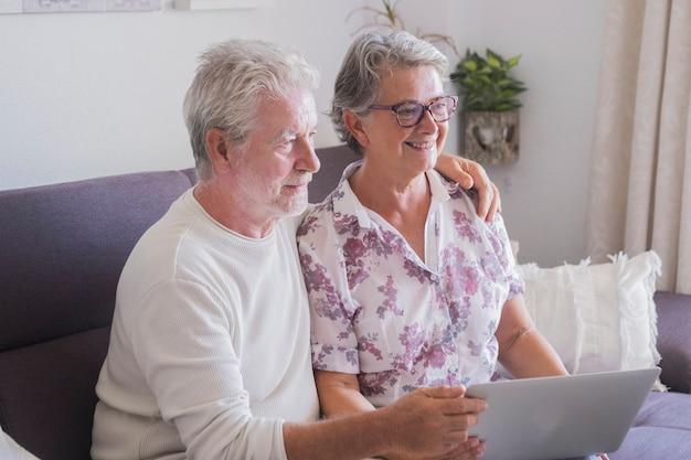 함께 노트북과 인터넷을 사용하는 집에서 노인 수석 성인의 백인 아름다운 커플