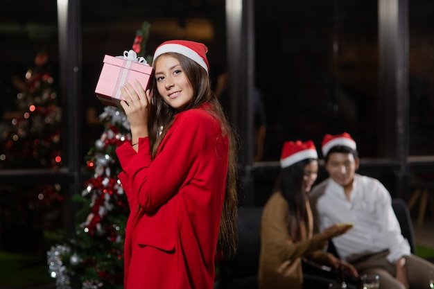 Caucasian beautiful girl holding gift boxes front of her colleagues for christmas party.
