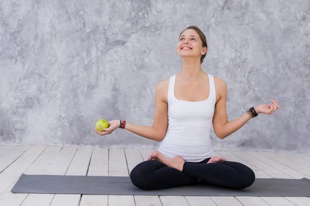 白人の美しい健康的な運動の陽気な女の子はトレーニングとカメラ目線の後青リンゴを食べる