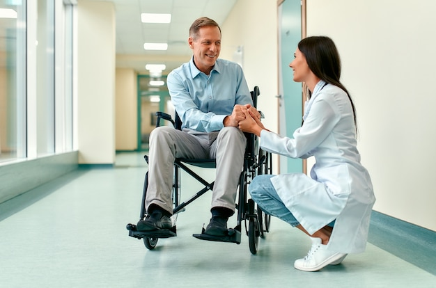 Caucasian beautiful nurse in medical uniform takes care of a mature male patient sitting on a wheelchair in the hospital, holding his hands.