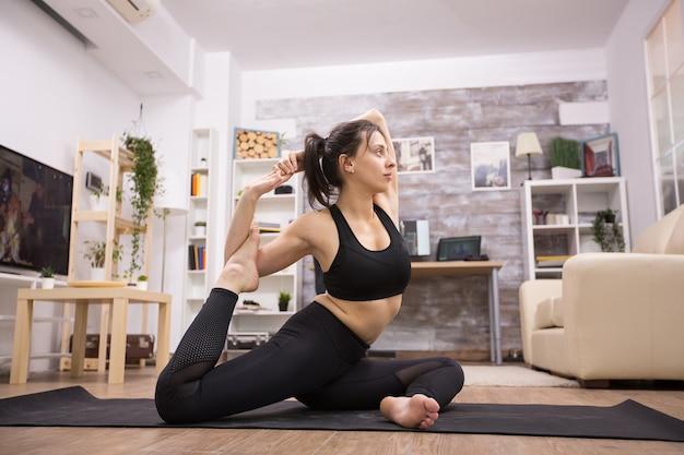 Caucasian beautiful practicing eka pada rajakapotasana yoga pose in living room.