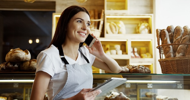 Caucasian beautiful woman baker or bread seller with a smile talking cheerfully on the phone while holding tablet device in hands and looking at its screen in the bakery shop. indoor