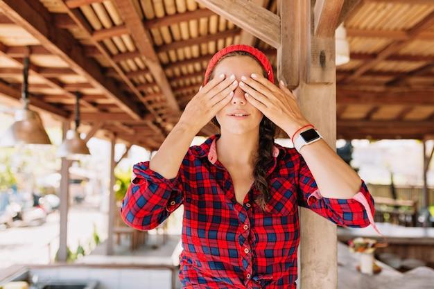 Bella donna caucasica con capelli scuri, pelle sana con trucco nudo pone alla macchina fotografica e viso chiuso con le mani in terrazza in legno