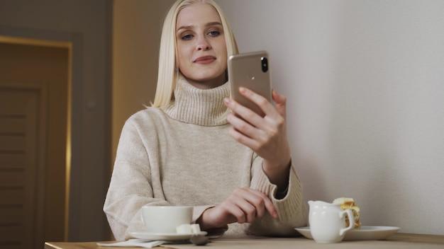 백인 아름 다운 젊은 여성 카페 테라스에서 siting 및 스마트 폰 음성 메시지 녹음. 세련 된 여자 얘기 하 고 휴대 전화에 오디오 기록을 보내는.