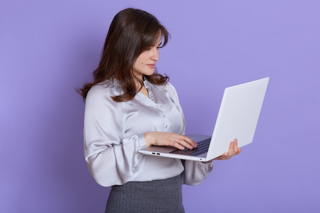Caucasian beautiful young woman with laptop in hands posing against lilac wall, looking at device screen, being concentrated while working, wearing elegant attire.