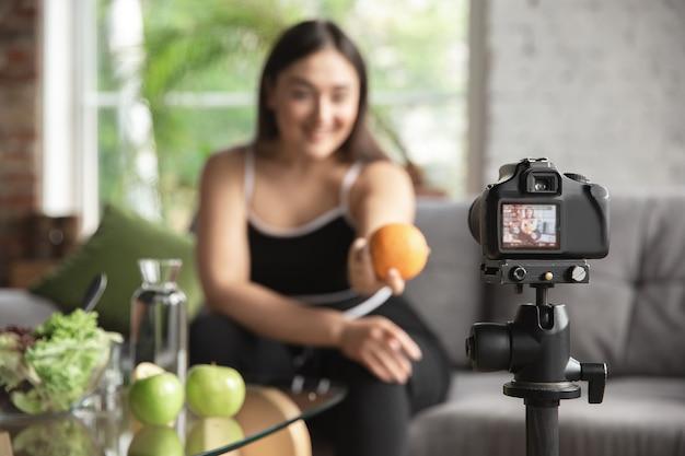 백인 블로거인 여성은 다이어트와 체중 감량 방법을 vlog로 만들고 몸에 긍정적이고 건강한 식생활을 합니다. 그녀의 유기농과 맛있는 요리법을 카메라를 사용하여 기록합니다.
