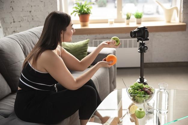 白人のブロガー、女性は、ダイエットと減量の方法をvlogで作成し、体をポジティブにし、健康的な食事をします。彼女の有機的でおいしいレシピを記録するカメラを使用します。