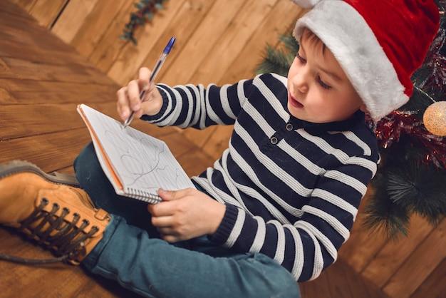 Кавказский белокурый мальчик в новогодней шапке пишет рождественские пожелания на деревянном фоне